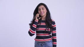 Mujer persa hermosa joven feliz que habla en el tel?fono metrajes