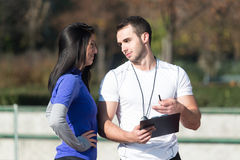 Mujer personal de Takes Notes While del instructor que ejercita afuera Fotografía de archivo