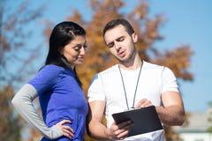 Mujer personal de Takes Notes While del instructor que ejercita al aire libre Foto de archivo libre de regalías