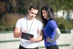 Mujer personal de Takes Notes While del instructor que ejercita al aire libre Imágenes de archivo libres de regalías
