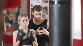 Mujer personal del entrenamiento del instructor en el entrenamiento del boxeo en club de deporte metrajes