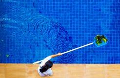 Mujer, personal que limpia la piscina de las hojas imágenes de archivo libres de regalías