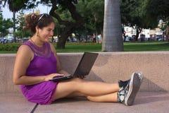 Mujer peruana joven con la computadora portátil en parque Imagenes de archivo