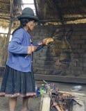 Mujer peruana nativa que prepara conejillos de Indias sobre el fuego Imagen de archivo libre de regalías