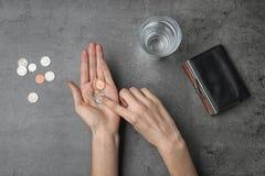 Mujer pobre que cuenta monedas en el fondo gris, visión superior imagen de archivo