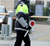 Mujer policía con la paleta mientras que tráfico de dirección Fotos de archivo
