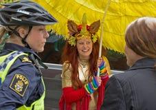 Mujer policía en el casco de la bicicleta, hablando con el participante del festival Foto de archivo libre de regalías