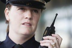 Mujer policía que comunica sobre su radio. Fotos de archivo