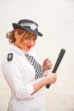 Mujer policía en uniforme con la matraca Fotografía de archivo