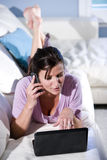 Mujer polivalente que habla en el teléfono usando la computadora portátil Imagenes de archivo