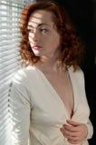 Mujer por la ventana con la luz a través de persianas Imágenes de archivo libres de regalías