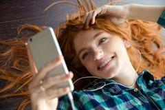Mujer positiva alegre del pelirrojo que escucha la música y la sonrisa Foto de archivo