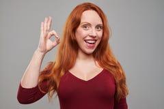 Mujer positiva con el pelo castaño que muestra gesto aceptable Fotos de archivo libres de regalías