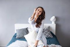 Mujer positiva con la almohada que se sienta en cama y que sonríe a la cámara en casa foto de archivo libre de regalías
