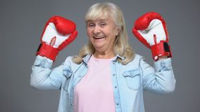 Mujer positiva del jubilado en manos de levantamiento de los guantes de boxeo para arriba, concepto del éxito, creencia almacen de video