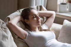 Mujer positiva joven que miente en el sofá que se relaja en casa imágenes de archivo libres de regalías