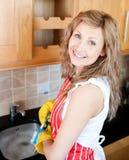 Mujer positiva que hace los platos imagen de archivo