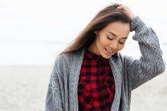 Mujer positiva que mira abajo mientras que camina en la playa Imagen de archivo libre de regalías