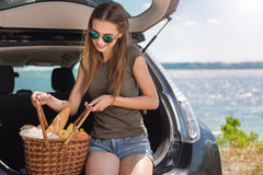 Mujer positiva que se sienta en el capo del coche fotografía de archivo libre de regalías