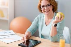 Mujer positiva que se sienta en la tabla Imagen de archivo