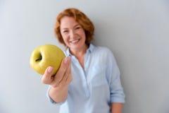 Mujer positiva que sostiene una manzana Imagen de archivo libre de regalías