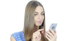 Mujer positiva que usa Smartphone para hojear, fondo blanco, jóvenes, almacen de metraje de vídeo