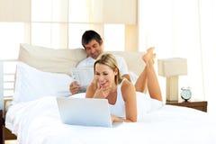 Mujer positiva que usa una computadora portátil que miente en cama Fotografía de archivo libre de regalías