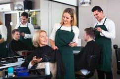 Mujer positiva sonriente que corta el pelo femenino del pensionista Imagen de archivo libre de regalías