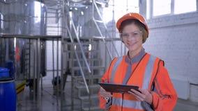 Mujer potente en la planta, hembra del obrero en el casco y guardapolvo con la tableta del ordenador que hace calculado almacen de metraje de vídeo