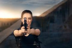 Mujer potente que apunta estilo de la película de acción del arma Imagenes de archivo