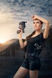 Mujer potente que lleva a cabo estilo de la película de acción del arma Fotografía de archivo libre de regalías