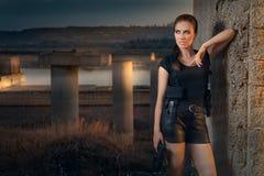 Mujer potente que lleva a cabo estilo de la película de acción del arma Imágenes de archivo libres de regalías