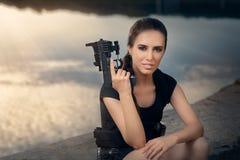 Mujer potente que lleva a cabo estilo de la película de acción del arma Fotos de archivo