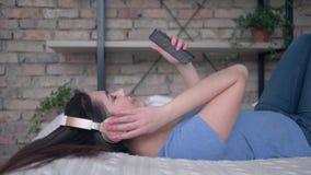 Mujer preciosa en los auriculares con música del placer del teléfono móvil mientras que descansa sobre cama en casa de vacacio almacen de metraje de vídeo