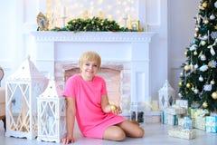 Mujer preciosa hermosa que se sienta en piso cerca de las linternas y de los controles foto de archivo libre de regalías