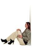Mujer preciosa joven que se sienta en piso y que se relaja Imagenes de archivo
