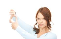 Mujer preciosa que crea un marco con los fingeres Imagen de archivo libre de regalías