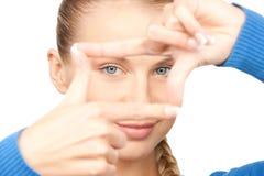 Mujer preciosa que crea un marco con los fingeres Fotografía de archivo