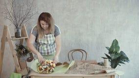 Mujer preciosa que embala el ramo comestible en el papel de Kraft almacen de video