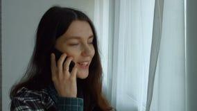 Mujer preciosa que invita al teléfono elegante cerca de ventana metrajes