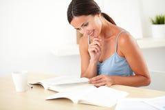Mujer preciosa que lee un libro en su escritorio imagen de archivo libre de regalías