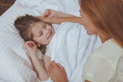 Mujer preciosa que mira su dormir de la hija fotografía de archivo