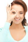 Mujer preciosa que mira a través del agujero de los fingeres Imagen de archivo
