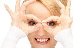 Mujer preciosa que mira a través del agujero de los fingeres Foto de archivo libre de regalías