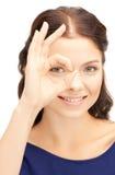Mujer preciosa que mira a través del agujero de los fingeres Fotografía de archivo libre de regalías