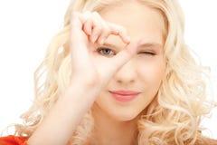 Mujer preciosa que mira a través del agujero de los fingeres Foto de archivo