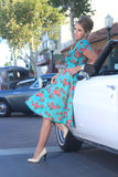 Mujer preciosa que presenta y y alrededor de un coche del vintage Foto de archivo