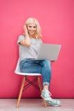 Mujer preciosa que se sienta en la silla con el ordenador portátil Foto de archivo