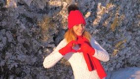Mujer preciosa que sonríe con las manos que hacen el corazón en el cuento al aire libre 4K del invierno almacen de metraje de vídeo