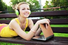 Mujer preciosa que tiene resto en el parque con la computadora portátil Foto de archivo